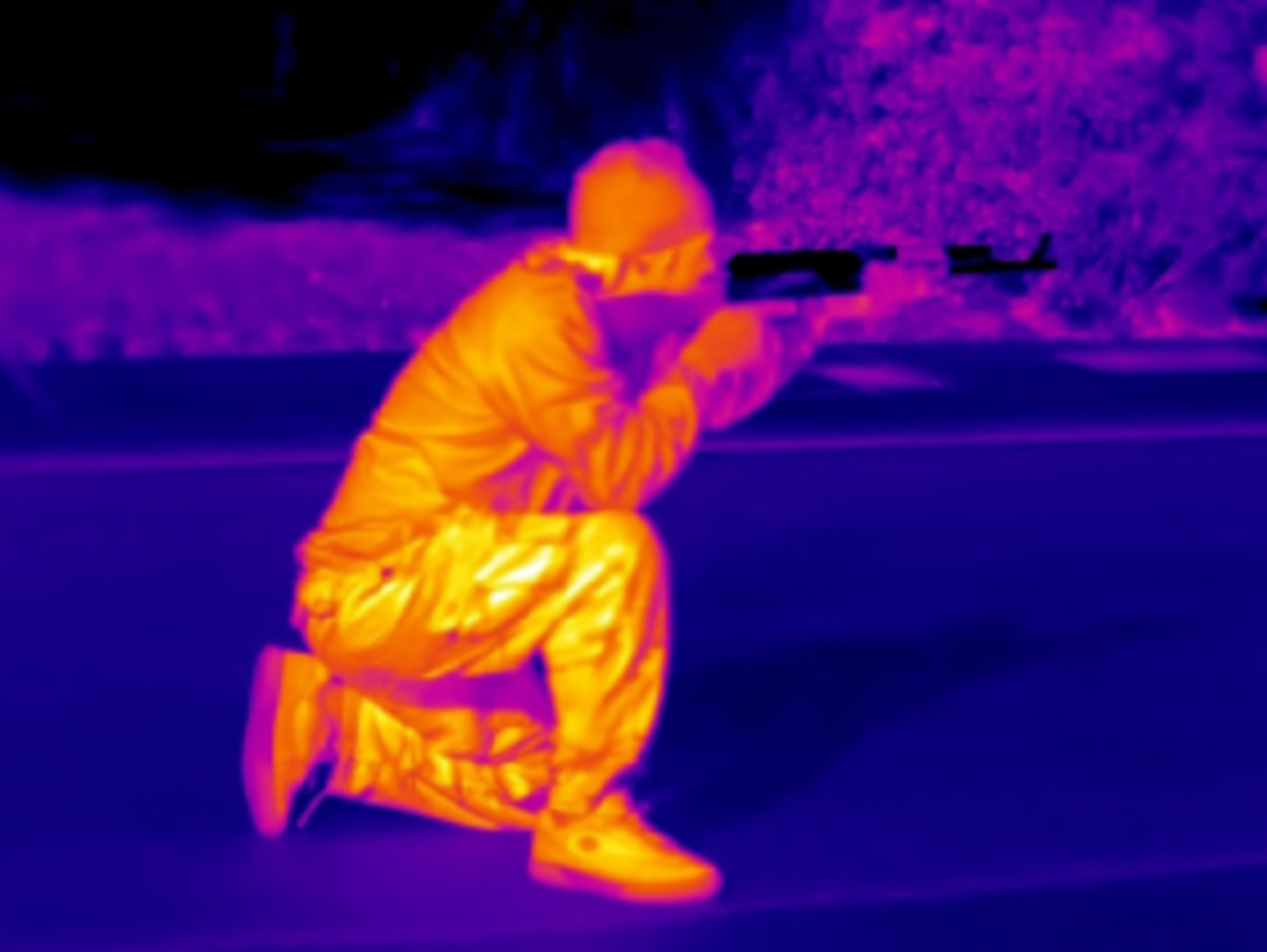 A thermal image of a man with a gun
